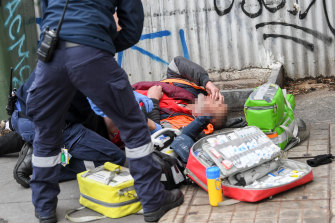 Paramedics attend to an overdose on Victoria Street last week.
