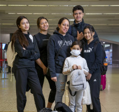 Moving back to Brissie: Meriana Ferris, centre, and her children at Melbourne Airport.