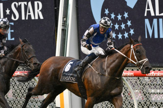 Hugh Bowman celebrates after steering Mugatoo to victory over Russian Camelot in the All-Star Mile at Moonee Valley.