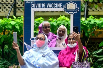 Women in Mumbai take post-vaccination selfies outside a hospital in March.