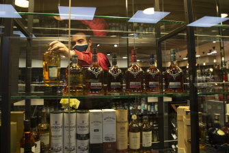 A man stocks a display shelf with bottles of alcohol at a Johannesburg liquor store.
