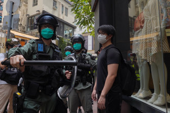 Police check pedestrians gathered in the Central district of Hong Kong on May 27.