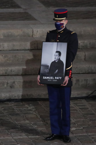 A Republican Guard holds a portrait of slain school teacher Samuel Paty during a memorial service in Paris.
