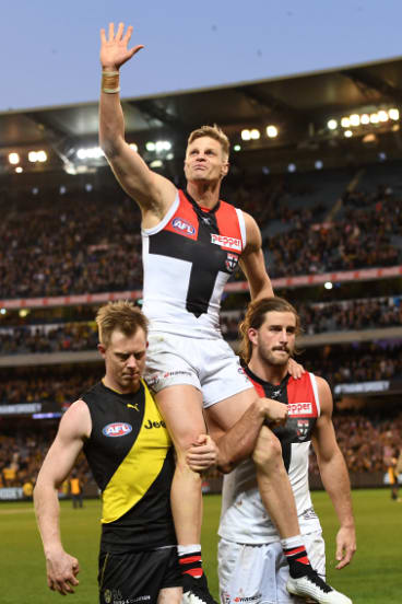 Nick Riewoldt of the Saints (centre) is chaired from the ground by his cousin Jack Riewoldt of the Tigers and Saints teammate Josh Bruce.