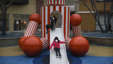 Chinese children wear protective masks as they play on a slide at a shopping mall in Beijing.