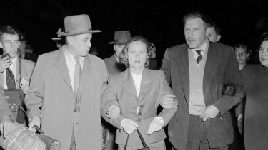 """""""Weeping and obviously near collapse, Mrs Petrov was tightly gripped by a Russian bodyguard who led her across the tarmac at Mascot last night. The Russian courier, Mr V. Karpinsky (left), who arrived from Moscow last Thursday, held Mrs Petrov's other arm."""""""