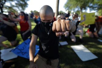Boris Garcia kneels for over eight minutes to remember George Floyd at a protest in Richardson, Texas.