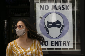 A woman walks out of a liquor store past a sign requesting customers wear a mask in Santa Monica, California.