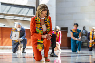 House Speaker Nancy Pelosi, centre, and other members of Congress, wear Kente cloth scarves while kneeling at the Capitol's Emancipation Hall, in Washington on Monday.