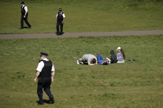 Police officers ask people to move on in Greenwich Park in London on Sunday.