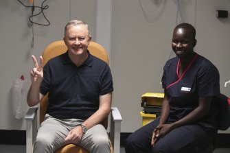 Opposition Leader Anthony Albanese gestures the 'V for vaccine' sign after receiving a COVID-19 vaccination.