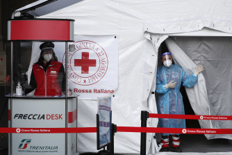 Paramedics wait to perform a COVID-19 swab test on passengers  outside Milan's central railway station in April.