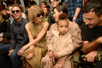 North, the daughter of Kim Kardashian West and Kanye West, sitting with her mother at a fashion show in 2015.