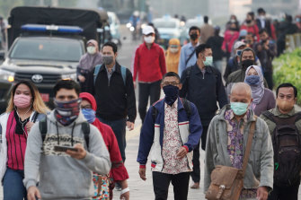 Commuters wear masks in Jakarta, Indonesia, on Friday. The country has the worst coronavirus outbreak in south-east Asia.