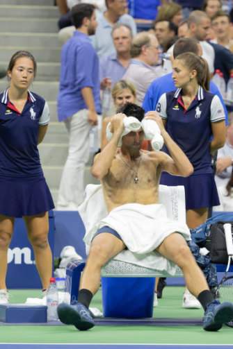 """Pre-ice bath: Djokovic uses a """"neck sausage"""" and damp lap towel to cool off during the US Open in 2018."""