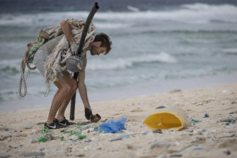 Marine conservationist Johnny Briggs finds a plastic drinking mug in the sand.
