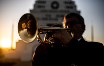Afghanistan war veteran Duncan Clements plays his bugle at dawn at the Parkes War Memorial.