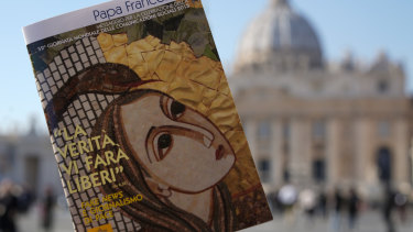 "Pope Francis book on ""Fake News"", is pictured in front of St. Peter's Basilica, in Rome."