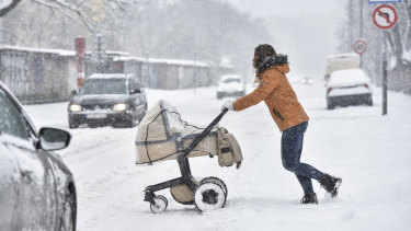 A woman pushes a pram across the street during heavy snowfall in Bratislava, Slovakia on Tuesday.