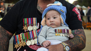 Baby Tyson observes the Anzac Day proceedings from the arms of his father Corey Van Wyngaarden.
