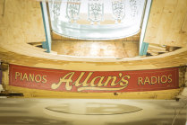 A remnant of Allan's music store sign on the upper wall of the ground floor.