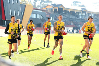 Richmond players run a lap of Punt Road Oval.