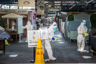 People in hazmat suits give Prahran Market a deep clean on Thursday.