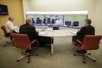 The national cabinet meets on Sunday nightL L-R foreground: Secretary of the Department of Prime Minister and Cabinet, Phil Gaetjens, Prime Minister Scott Morrison and Chief Medical Officer Professor Brendan Murphy, speak with NSW Premier Gladys Berejiklian (on screen).