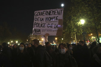 "A protester holds a poster reading ""Government of shame, Police of fear"" during a rally on the Place de La Republique on Tuesday, a day after police ejected migrants by force."