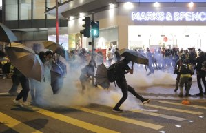 A protester kicks a police tear gas shell away during clashed outside a shopping centre in Hong Kong on Sunday.
