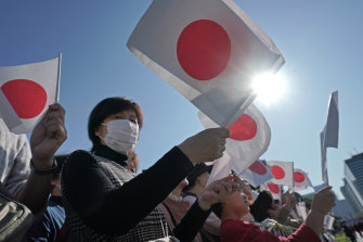 A Japanese well-wisher holds a national flag - called nisshoki or hinomaru - at the Imperial Palace before the royal motorcade of Emperor Naruhito and Empress Masako in Tokyo in 2019.