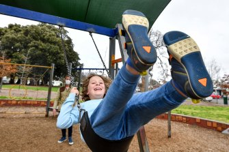 Toby Cummings' son Louis. 8, enjoys his last swing at a public playground for at least two weeks on Monday.