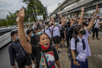 Pro-democracy protesters flash three-fingered salutes during a demonstration in Bangkok.