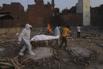 Family members and volunteers carry the body of a COVID-19 victim before cremation in New Delhi in May.