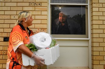 Tharawal Aboriginal Corporation case worker Kim Bell delivers groceries to 73-year-old Ivan Wellington.