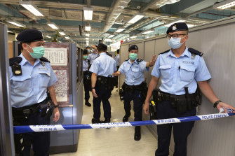 Police officers set up cordon line inside the Apple Daily newspaper headquarters.
