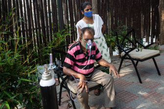 A daughter pats the back of her father as he struggles to breathe with the aid of supplemental oxygen in Bengaluru, India.