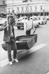 Photographer Fred Murray found Brian Griffiths (left) and Peter Williamson carrying their six-foot dinghy at Circular Quay. They'd rowed across harbour from Mosman, landed at Mrs. Macquarie's chair, and were carrying the boat up town. Then workmen at Circular Quay volunteered to mind the dinghy until the boys row home tonight. May 21, 1969.