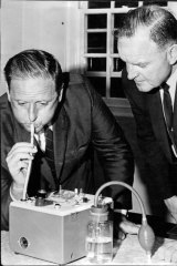 Milton Morris (left) and Insp A. Douglas test a breathalyser at a road safety meeting in 1968.