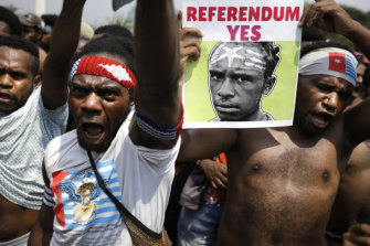 A Papuan activist displays a banner demanding a referendum during a rally near the presidential palace in Jakarta.