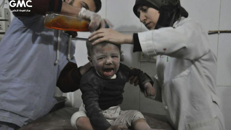 Paramedics treat a Syrian child who was wounded during airstrikes and shelling by Syrian government forces in Ghouta.