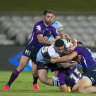 Braden Hamlin-Uele of the Sharks is tackled during the round-two match against the Storm.