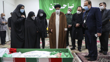 Iran's Judiciary Chief Ayatollah Ebrahim Raisi pays his respect to the body of slain scientist Mohsen Fakhrizadeh among his family, in Tehran, Iran, on Saturday.