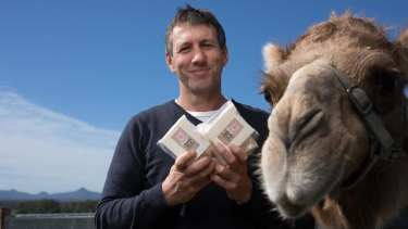 Summer Land Camels' Jeffrey Flood with the farm's camel cheddar.