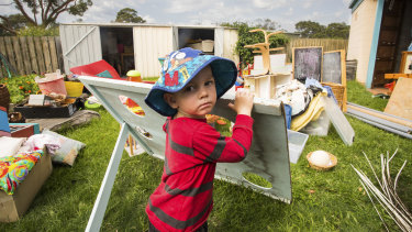 Mallacoota preschooler Tom Brownlie watches on as mould-damaged equipment is thrown away on Monday.
