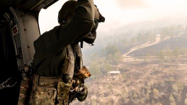 Leading Seaman Aircrewman Benjamin Nixon maintains a lookout during a search and rescue flight in fire-stricken NSW.