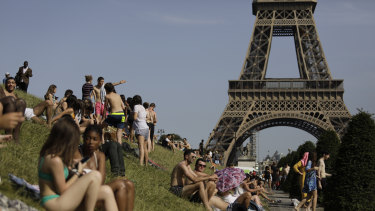 People enjoy the sun on the Trocadero gardens near the Eiffel Tower in Paris.