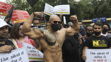 A member of Indian Gym's Welfare Federation flexes his muscles as they block a road during a protest in New Delhi, India.
