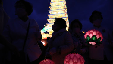 Buddhist believers hold colourful lotus lanterns as they pray around a lantern tower in the shape of a Buddhist temple pagoda on the birthday of Buddha at Gwanghwamun Plaza in Seoul, South Korea.