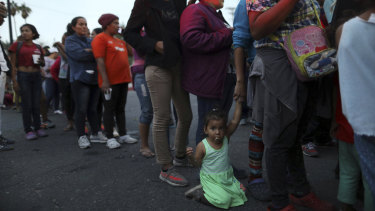 Central American migrants, as part of the Central American caravan trying to reach the United States, wait to receive donated dinner downtown in Mexicali, Mexico.